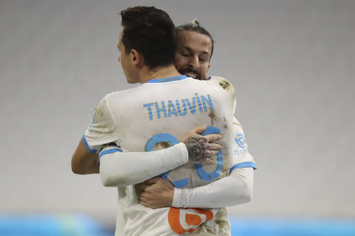 Marseille's Florian Thauvin celebrates his goal with his teammate Dario Benedetto against Rennes during the French League One soccer match between Marseille and Reims at the Stade Velodrome in Marseille, southern France, Saturday Dec. 19, 2020. (AP Photo/Daniel Cole)