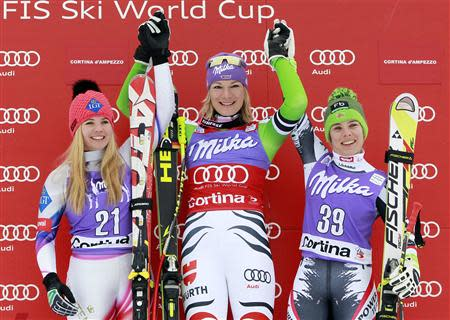 Maria Hoefl-Riesch of Germany (C) celebrates on the podium with second place Tina Weirather of Liechtenstein (L) and third place Nicole Schmidhofer of Austria, after winning the women's FIS World Cup Downhill race in Cortina D'Ampezzo January 24, 2014. REUTERS/Alessandro Garofalo