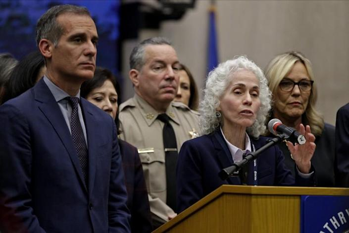FILE - In this March 12, 2020 file photo Los Angeles County Public Health Director Barbara Ferrer, at podium, speaks at a news conference with Los Angeles Mayor Eric Garcetti, left, in Los Angeles. The U.S. Department of Justice on Friday, May 22, 2020, warned the mayor of Los Angeles and Ferrer, the county's top health officer that an extension of the coronavirus stay-at-home order may be unlawful. The vague letter sent to Garcetti and Ferrer did not spell out any specific violations, but noted concern about statements both had made publicly that restrictions may be prolonged without a vaccine. (AP Photo/Damian Dovarganes,File)
