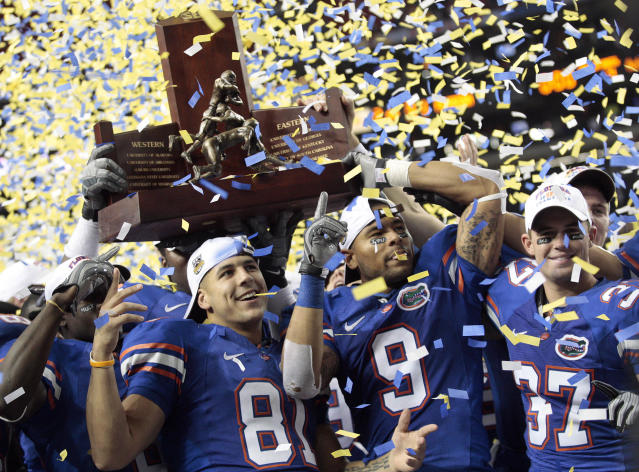 FILE - In this Saturday, Dec. 6, 2008, file photo, the Florida Gators, from left, Aaron Hernandez (81), Louis Murphy (9) and Butch Rowley (37) celebrate after receiving the SEC Championship Trophy following a 31-20 win over top-ranked Alabama in the Southeastern Conference Championship NCAA college football game at the Georgia Dome in Atlanta. Hernandez, who was serving a life sentence for a murder conviction and just days ago was acquitted of a double murder, died after hanging himself in his prison cell Wednesday, April 19, 2017, Massachusetts prisons officials said. (AP Photo/Dave Martin, File)