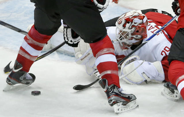 Austria goaltender Bernhard Starkbaum drops to the ice to smother a rebound against Finland in the first period of a men's ice hockey game at the 2014 Winter Olympics, Thursday, Feb. 13, 2014, in Sochi, Russia. (AP Photo/Mark Humphrey)