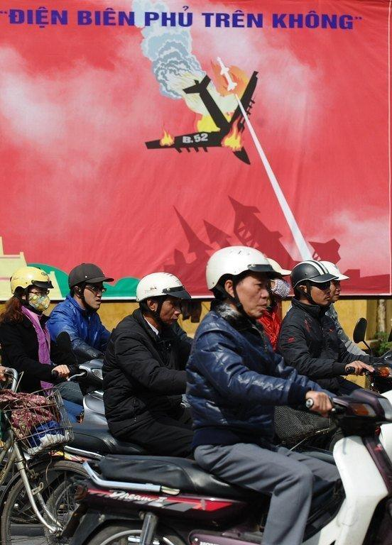 Posters of US bombers crashing in flames festoon Hanoi to mark another anniversary in a long-finished war, December 21, 2012. But behind the usual propaganda Vietnam's rulers face a modern-day threat -- anger over the economy