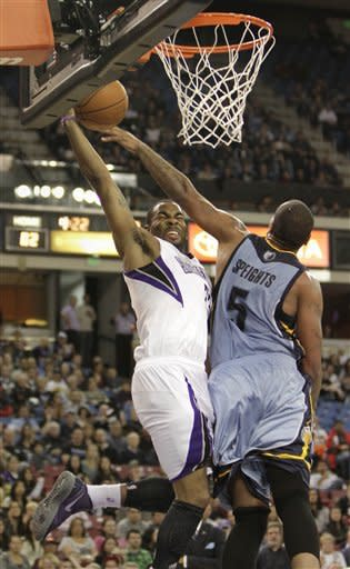 Sacramento Kings guard Marcus Thornton, left, is fouled by Memphis Grizzlies forward Marreese Speights, as he drives to the basket during the second half of an NBA basketball game in Sacramento, Calif., Tuesday, March 20, 2012. The Kings won 119-110.(AP Photo/Rich Pedroncelli)