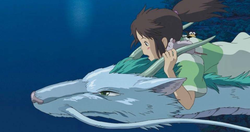 Chihiro rides on Haku's back as he flies them home. (Studio Ghibli)