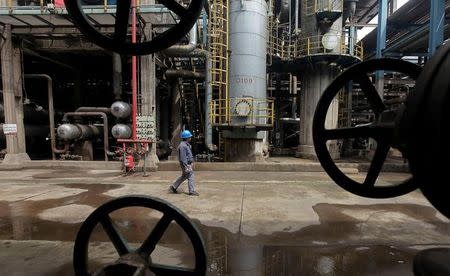 A worker walks past oil pipes at a refinery in Wuhan, Hubei province
