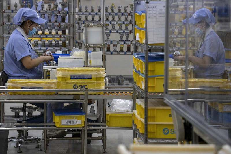 In this Wednesday, May 13, 2020, photo, a worker at SMC China, a Japanese joint venture pneumatic engineering company, assembles products at a factory in Beijing. The United States, Japan and France are prodding their companies to rely less on China to make the world's smartphones, drugs and other products. But even after the coronavirus derailed global trade, few are willing to give up access to its skilled workers, vast market and efficient suppliers by moving factories closer to home. (AP Photo/Ng Han Guan)