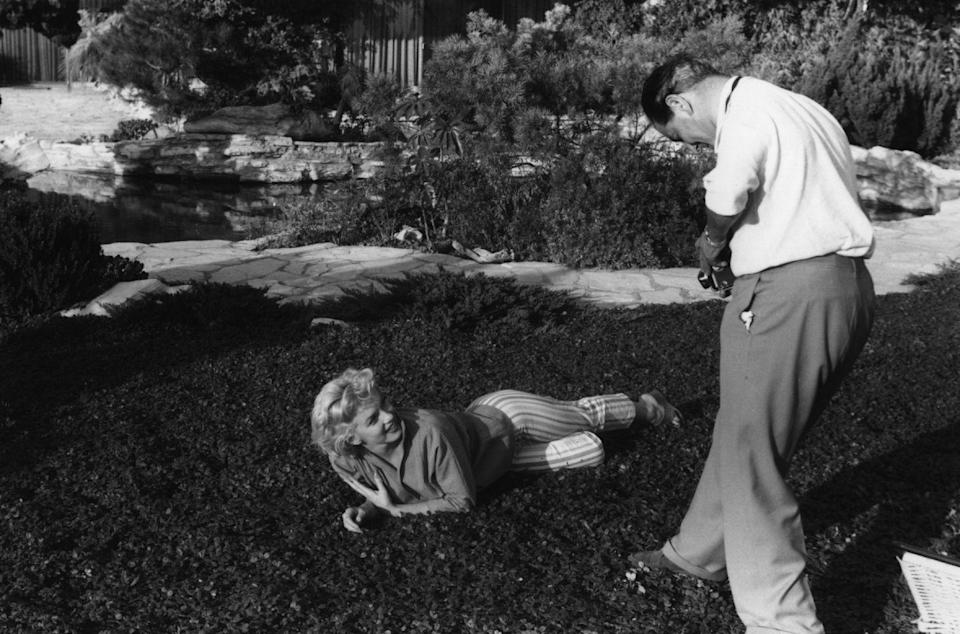 """<p>Hollywood bombshell Marilyn Monroe poses for a photographer in the backyard of her Palm Springs home. Later that year, Monroe filmed the iconic """"<a href=""""https://www.biography.com/news/marilyn-monroe-seven-year-itch-dress-photos"""" rel=""""nofollow noopener"""" target=""""_blank"""" data-ylk=""""slk:flying skirt"""" class=""""link rapid-noclick-resp"""">flying skirt</a>"""" scene from the film,<em> The Seven Year Itch</em>.</p>"""