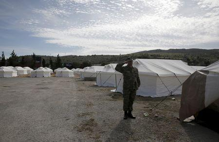 A Greek soldier salutes as he stands next to tents at a newly operational relocation camp for refugees in Schisto, near Athens, Greece, February 16, 2016. REUTERS/Alkis Konstantinidis