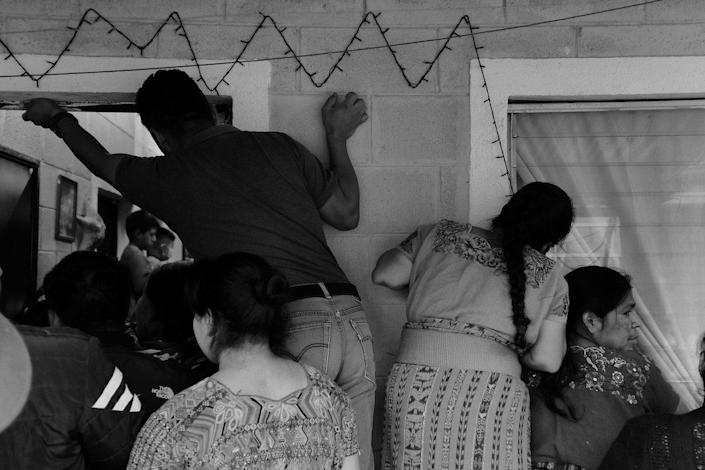Family members and neighbours of Baltazar Gomez Toma watch as members of the Forensic Anthropology Foundation of Guatemala (FAFG) arrange his skeletal remains. Cotzal, Quiche, Guatemala. February 10, 2021.