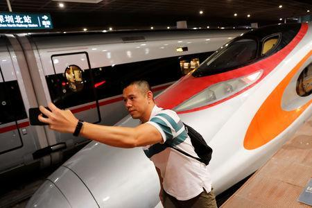 A passenger poses next to the first train that departed from Hong Kong during the first day of service of the Hong Kong Section of the Guangzhou-Shenzhen-Hong Kong Express Rail Link, in Shenzhen, China September 23, 2018. REUTERS/Tyrone Siu