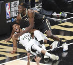 Milwaukee Bucks forward Giannis Antetokounmpo (34) grimaces as he falls next to Atlanta Hawks center Clint Capela during the second half in Game 4 of the NBA basketball Eastern Conference finals in Atlanta on Tuesday, June 29, 2021. Antetokounmpo hobbled off the court with an injured left knee. (Curtis Compton/Atlanta Journal-Constitution via AP)