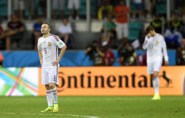Spain's Andres Iniesta, left, reacts after the 4th Dutch goal during the group B World Cup soccer match between Spain and the Netherlands at the Arena Ponte Nova in Salvador, Brazil, Friday, June 13, 2014. (AP Photo/Manu Fernandez)