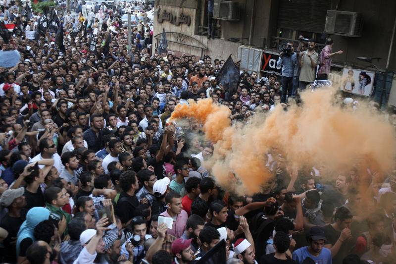 Protesters chant slogans amid orange smoke outside the U.S. embassy in Cairo, Egypt, Tuesday, Sept. 11, 2012. Egyptian protesters, largely ultra conservative Islamists, have climbed the walls of the U.S. embassy in Cairo, went into the courtyard and brought down the flag, replacing it with a black flag with Islamic inscription, in protest of a film deemed offensive of Islam. (AP Photo/Mohammed Abu Zaid)