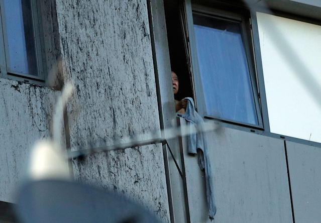 <p>A person peers out of a window from a building on fire in London, Wednesday, June 14, 2017. Metropolitan Police in London say they're continuing to evacuate people from a massive apartment fire in west London. The fire has been burning for more than three hours and stretches from the second to the 27th floor of the building. (Matt Dunham/AP) </p>