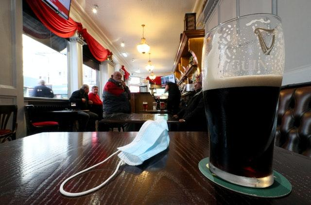 A close up of a pint of Guinness and a face mask on a table in the Richmond pub in Liverpool (Peter Byrne/PA)
