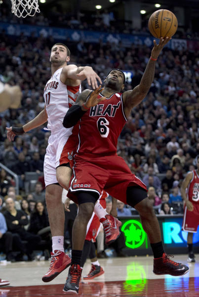 Miami Heat forward LeBron James, RIGHT, drives to the hoop against Toronto Raptors centre Jonas Valanciunas during second half NBA action in Toronto Sunday Feb. 3, 2013. (AP Photo/THE CANADIAN PRESS, Frank Gunn)