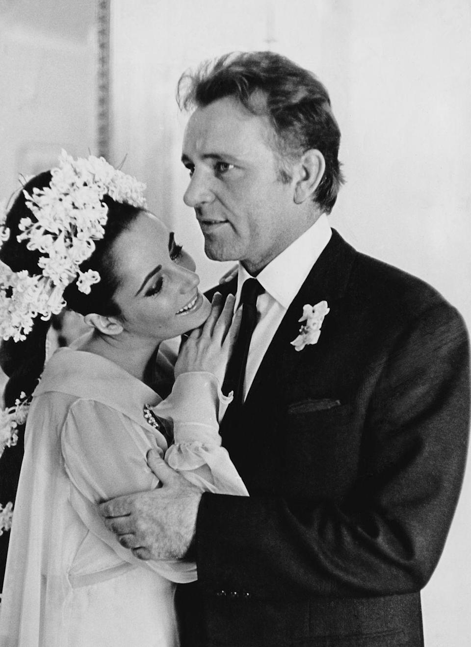 <p>Elizabeth wore a marigold, long sleeve dress and an elaborate white flowered hairpiece for her wedding to Richard Burton in Montreal, Canada. </p>