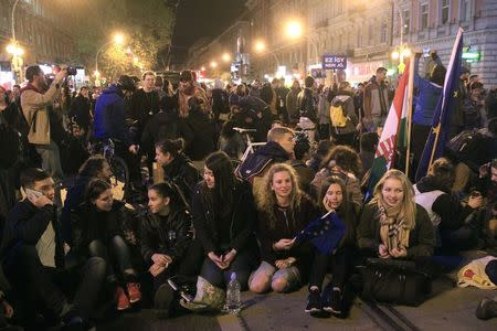 People sit during a  protest against a new law that would undermine Central European University in Budapest