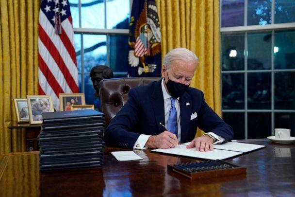 PHOTO: President Joe Biden signs his first executive order in the Oval Office of the White House in Washington, Jan. 20, 2021. (Evan Vucci/AP, FILE)