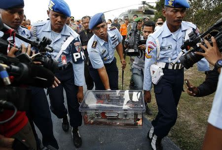 Military policemen carry the flight data recorder of AirAsia QZ8501 at the airbase in Pangkalan Bun, Central Kalimantan January 12, 2015. REUTERS/Darren Whiteside