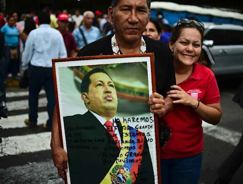 Supporters of President Nicolas Maduro hold a portrait of late Venezuelan president Hugo Chavez outside the National Assembly on January 15, 2016 (AFP Photo/Ronaldo Schemidt)