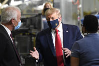 President Donald Trump, center, wears a mask as he talks to Jim Keppler, Whirlpool Corporation Vice President of Integrated Supply Chain and Quality, left, during a tour of the Whirlpool Corporation facility in Clyde, Ohio, Thursday, Aug. 6, 2020. (AP Photo/Susan Walsh)