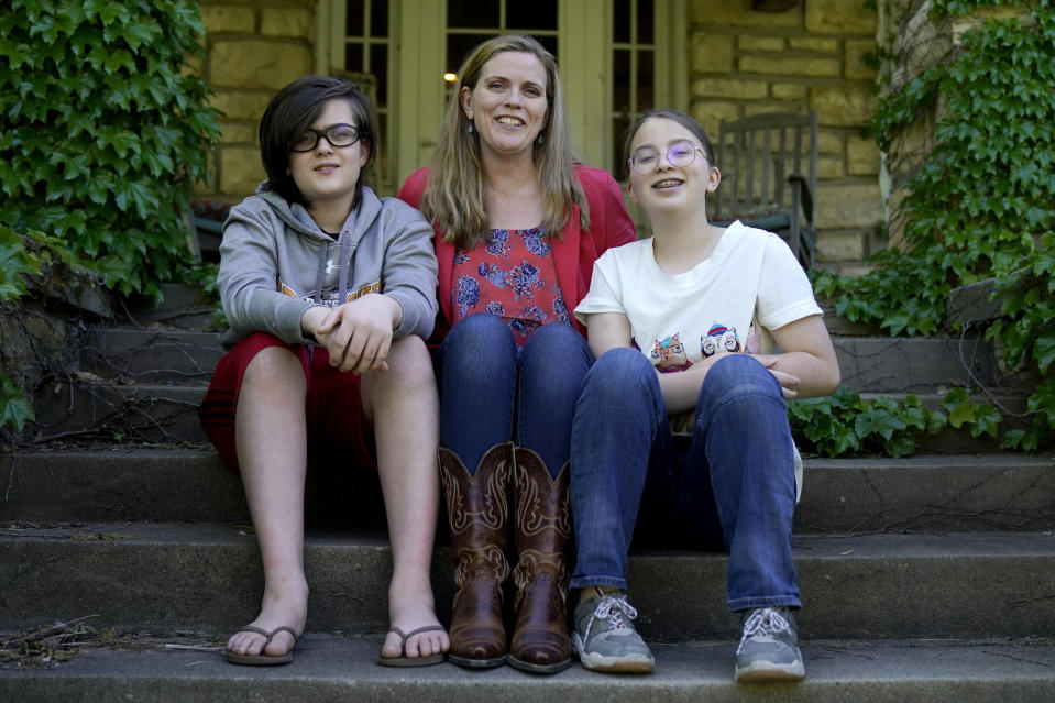 Heather Ousley sits with her older children Elliannah, 15, right, and Samuel, 13, in front of their home in Merriam, Kan, Tuesday, May 4, 2021. Ousley was thrilled when she heard the FDA was expected to authorize Pfizer's COVID-19 vaccine for youngsters ages 12 to 15 and was hoping to get her kids vaccinated as soon as she can. (AP Photo/Charlie Riedel)