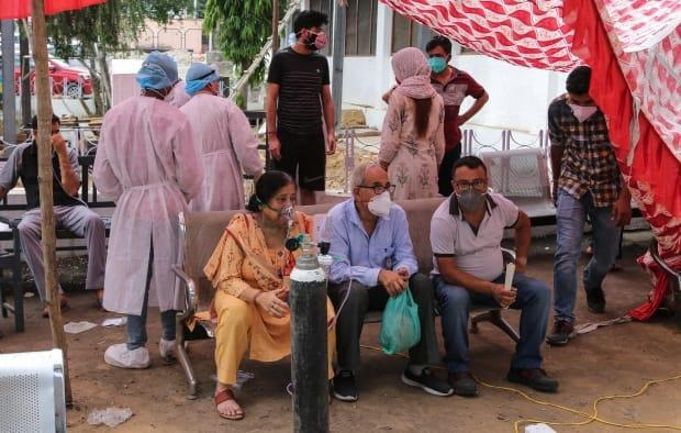 COVID-19 patients receive oxygen outside a government run hospital in Jammu, India, Wednesday, May 12, 2021. (Channi Anand/Associated Press - image credit)