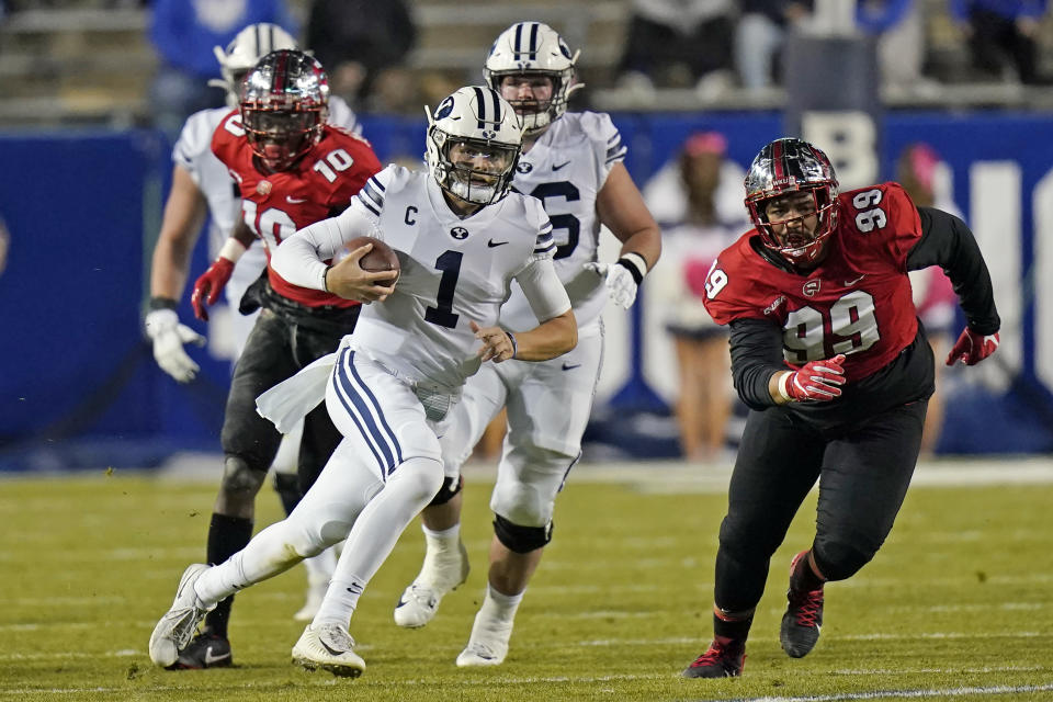 FILE - In this Saturday, Oct. 31, 2020, file pool photo, BYU quarterback Zach Wilson (1) carries the ball in the first half of an NCAA college football game against Western Kentucky in Provo, Utah. An unusual college football season has produced some unexpected unbeaten teams dotting the AP Top 25 with about a month left. Led by No. 7 Cincinnati and No. 8 BYU, five teams from outside the Power Five conferences have yet to lose. (AP Photo/Rick Bowmer, Pool, File)