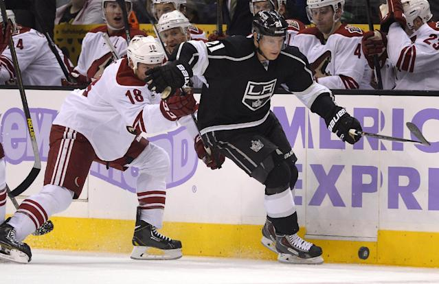 Los Angeles Kings right wing Matt Frattin, right, and Phoenix Coyotes left wing David Moss battle for the puck during the second period of their NHL hockey game, Thursday, Oct. 24, 2013, in Los Angeles. (AP Photo/Mark J. Terrill)