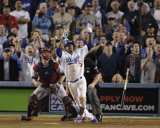 Los Angeles Dodgers' Juan Uribe watches his two-run home run in front of Atlanta Braves catcher Brian McCann and home plate umpire Bill Miller during the eighth inning of Game 4 in the National League baseball division series, Monday, Oct. 7, 2013, in Los Angeles. The Dodgers won 4-3, and advanced to the NL championship series. (AP Photo/Jae C. Hong)