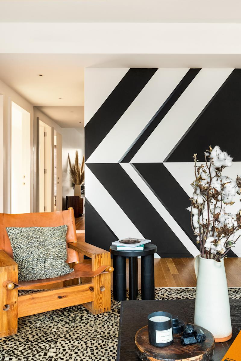 In the living room, Chris Wyrick designed a wall mural inspired by the architecture of Brazilian modernist Oscar Niemeyer. Børge Mogensen chair; side table by Matter.
