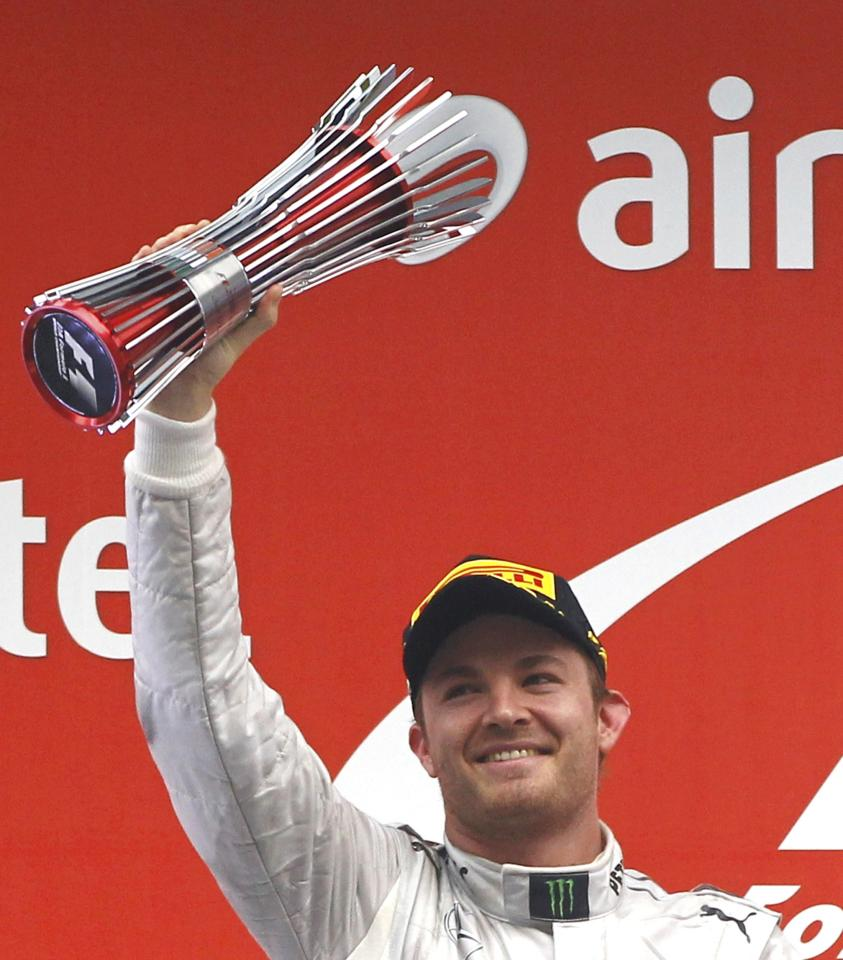 Mercedes Formula One driver Nico Rosberg of Germany celebrates with his trophy after placing second in the Indian F1 Grand Prix at the Buddh International Circuit in Greater Noida, on the outskirts of New Delhi, October 27, 2013. REUTERS/Adnan Abidi (INDIA - Tags: SPORT MOTORSPORT F1)