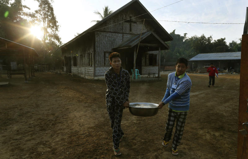 In this photo taken on Feb 12, 2013, two young rehab patients carry breakfast for camp residents at the Kachin Baptist Convention's rehabilitation camp in Myitkyina, the provincial capital of Kachin state, Myanmar. Myitkyina is known for having one of the highest concentrations of drug addicts in the world. The Kachin Baptist Convention, an evangelical group with over 300 churches in the state, says nearly 80 percent of ethnic Kachin youth are addicts. Their drug of choice is heroin. In the shadow of war, even drug abuse becomes politicized. Gryung Heang, the pastor of the camp church, says the government is willfully turning a blind eye to drug abuse among the Kachin because it wants to decimate young potential fighters. Officials say such views are absurd. (AP Photo/Gemunu Amarasinghe)