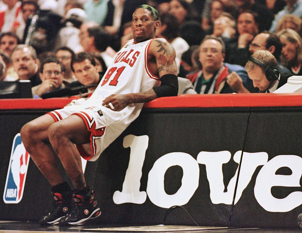 CHICAGO, UNITED STATES:  Dennis Rodman of the Chicago Bulls leans on the scorers table as he waits to come into the game against the Utah Jazz 10 June in game four of the NBA Finals at the United Center in Chicago, IL. Rodman hit four free throws down the stretch to lead the Bulls as they beat the Jazz 86-82 to lead the best-of-seven series 3-1.        AFP PHOTO/Jeff HAYNES  (Photo credit should read JEFF HAYNES/AFP via Getty Images)