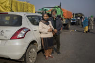 "Dharam Singh Sandhu, 67, and his wife Nirmaljeet Singh Kaur, 66, stand for a photograph next to their car where they are spending nights parked near the site of a protest against new farming laws, at the Delhi-Haryana state border, India, Tuesday, Dec. 1, 2020. In the morning, they share breakfast at a makeshift soup kitchen. The latter part of the day is spent taking part in the demonstrations. ""Our land is our mother. If we can't protect it then we have no right to live,"" Sandhu said about the protests. ""Our country is like a bunch of flowers, but Modi wants it to be of the same color. He has no right to do that. I am here to protest against that mindset,"" Kaur said. (AP Photo/Altaf Qadri)"