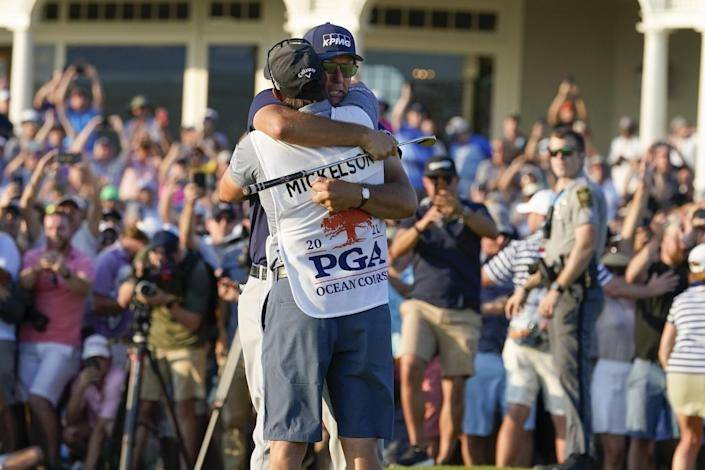 Phil Mickelson hugs his caddie after winning the PGA Championship on Sunday.