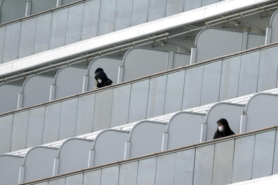 Masked passengers stand outside on the balcony of the cruise ship Diamond Princess anchored at Yokohama Port in Yokohama, near Tokyo. Friday, Feb. 7, 2020. Japan on Friday reported 41 new cases of a virus on the cruise ship that's been quarantined. About 3,700 people have been confined aboard the ship. (AP Photo/Eugene Hoshiko)