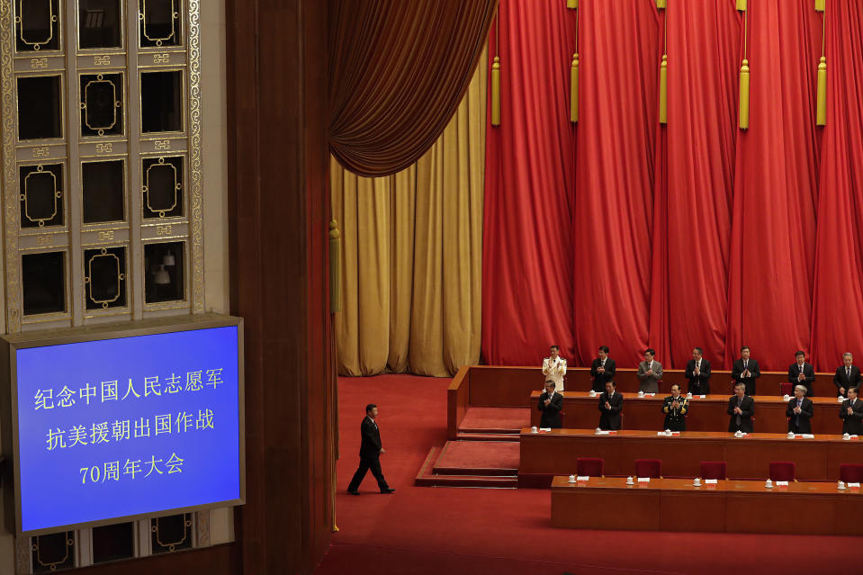 Party officials applaud as Chinese President Xi Jinping, left, arrives for the commemorating conference on the 70th anniversary of the Chinese army entering North Korea to resist the US army, at the Great Hall fo the People in Beijing, Friday, Oct. 23, 2020. (AP Photo/Andy Wong)