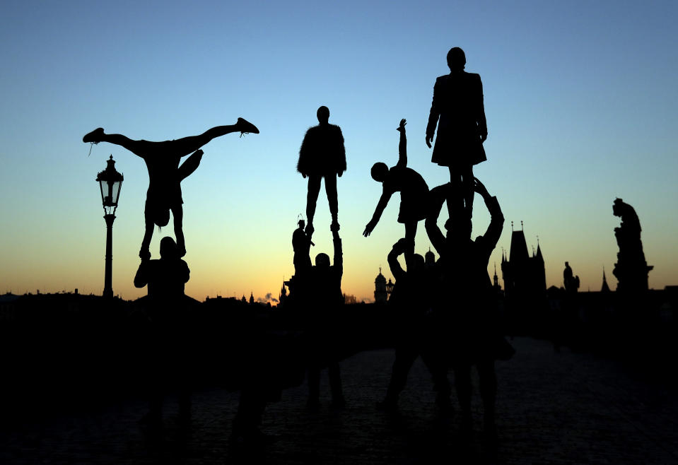 Street artists are silhouetted against the rising sun as they perform on the near empty Charles Bridge in Prague, Czech Republic, Thursday, April 2, 2020. The Czech Republic's government has approved further dramatic measures to try and stem the spread of the novel coronavirus called COVID-19. The coronavirus causes mild or moderate symptoms for most people, but for some, especially older adults and people with existing health problems, it can cause more severe illness or death. (AP Photo/Petr David Josek)