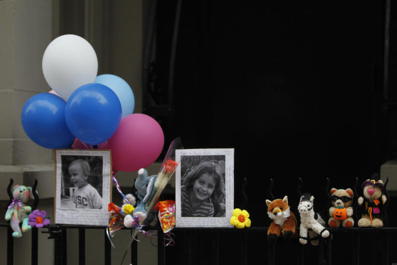 Photographs of the two children allegedly stabbed by their nanny are displayed alongside balloons and stuffed animals at memorial outside the apartment building were they lived, Saturday, Oct. 27, 2012 in New York. The 2-year-old son and 6-year-old daughter of a CNBC executive were found dead by their mother in a dry bathtub in the family's Upper West Side apartment Thursday night. The nanny suspected of stabbing the children was in critical condition Friday with apparently self-inflicted injuries. (AP Photo/Mary Altaffer)