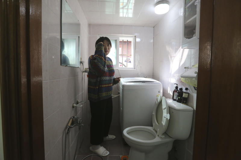"""Kim Da-hye, a 29-year-old South Korean, explains about the restroom, in her semi-basement apartment in Seoul, South Korea, Saturday, Feb. 15, 2020. For many South Koreans, the image of a cramped basement apartment portrayed in the Oscar-winning film """"Parasite"""" rings true, bringing differences in their social status to worldwide attention.(AP Photo/Ahn Young-joon)"""