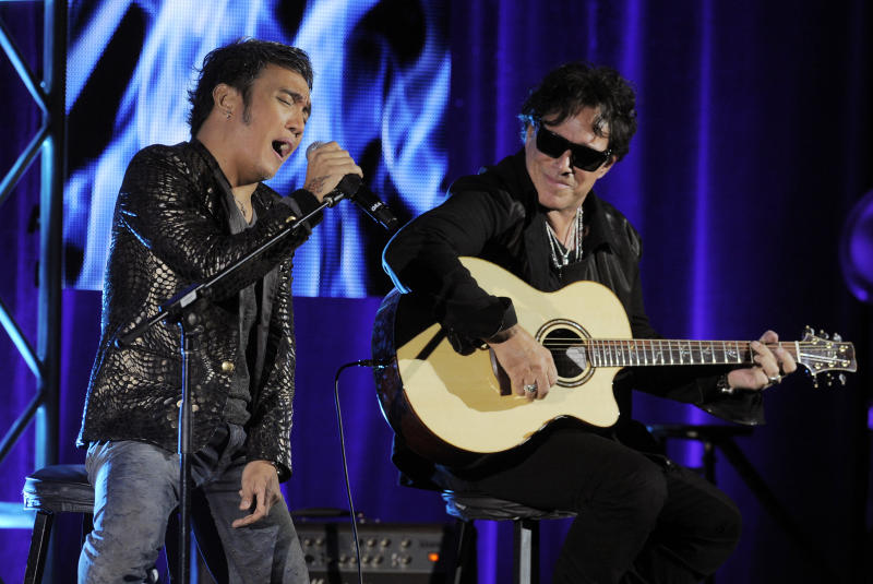 """Arnel Pineda, left, and Neal Schon of the rock band Journey perform onstage following a panel discussion on the Independent Lens documentary """"Don't Stop Believin': Everyman's Journey,"""" at the PBS Summer 2013 TCA press tour at the Beverly Hilton Hotel on Tuesday, August 6, 2013 in Beverly Hills, Calif. (Photo by Chris Pizzello/Invision/AP)"""