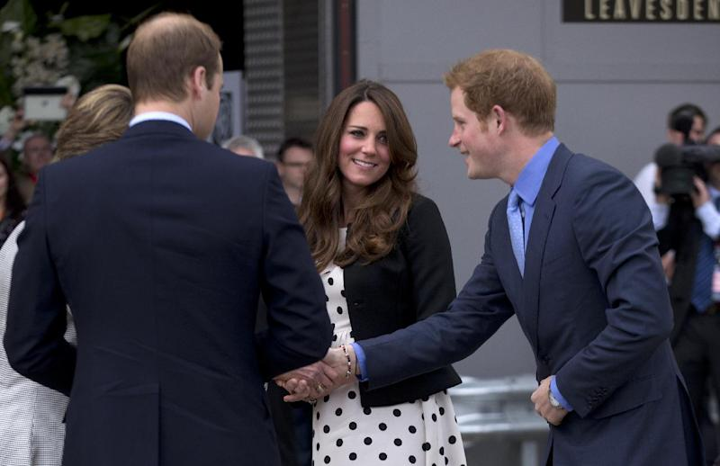"""Britain's Kate the Duchess of Cambridge stands with her husband Prince William, left, and his brother Prince Harry, right, as they are greeted upon their arrival to attend the inauguration of """"Warner Bros. Studios Leavesden"""" near Watford, approximately 18 miles north west of central London, Friday, April 26, 2013. As well as attending the inauguration Friday at the former World War II airfield site, the royals will undertake a tour of Warner Bros. """"Studio Tour London - The Making of Harry Potter"""", where they will view props, costumes and models from the Harry Potter film series. (AP Photo/Matt Dunham)"""