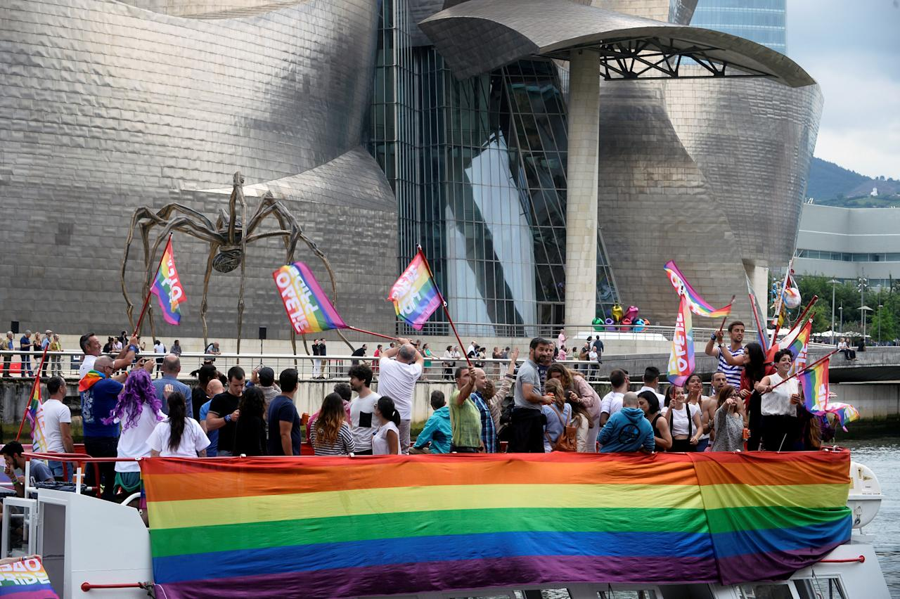 "People wave rainbow flags on board a boat during the ""Parade For Equality"", ahead of WorldPride, an event promoting LGBT issues, on the Nervion River in front of the Guggenheim Museum Bilbao in Bilbao, Spain June 24, 2017. REUTERS/Vincent West"
