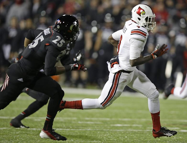 Louisville wide receiver DeVante Parker, right, runs past Cincinnati safety Arryn Chenault (25) for a 36-yard touchdown on a pass reception in the first half of an NCAA college football game on Thursday, Dec. 5, 2013, in Cincinnati. (AP Photo/Al Behrman)
