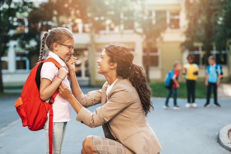 Mother and daughter outside school