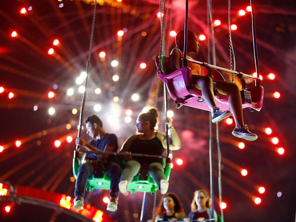 People hang from the Sky Flyer ride at the State Fair Meadowlands during a Fourth of July fireworks display in 2015.
