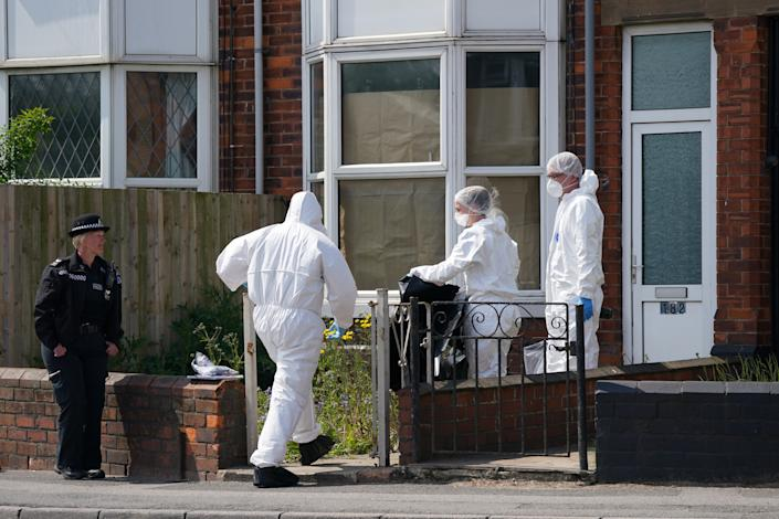 Police officers at the scene in High Holme Road, Louth, Lincolnshire, following the death of a woman and child on Monday. An urgent appeal has been issued by police to find Daniel Boulton, 29, in connection with the incident. Picture date: Tuesday June 1, 2021.