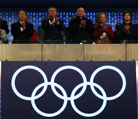 Secretary-General of the United Nations Ban Ki-moon (L), International Olympic Committee President Thomas Bach (2nd L) and President of Russia Vladimir Putin applaud during the opening ceremony of the 2014 Sochi Winter Olympics, February 7, 2014. REUTERS/Brian Snyder